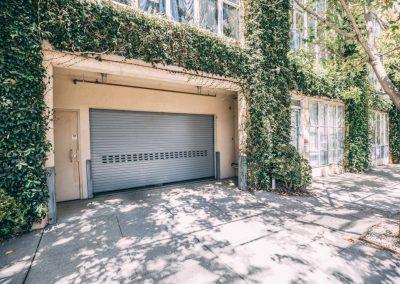 Commercial overhead door installed in building with vines on exterior