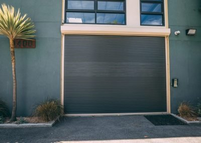 Overhead rolling commercial door installed on building wall next to palm tree