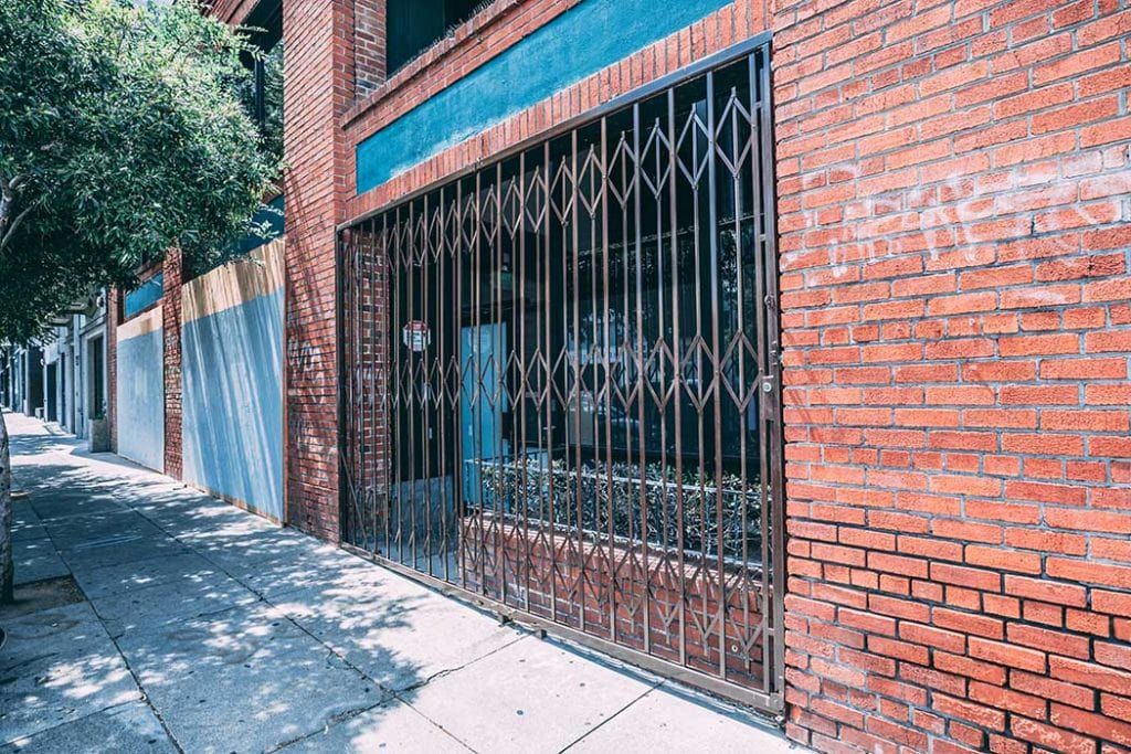 Accordion gate installed for brick building