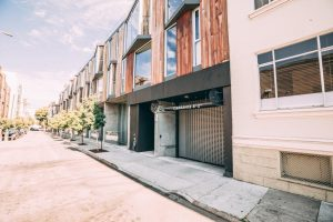 Commercial overhead metal grille door installation on San Francisco strip